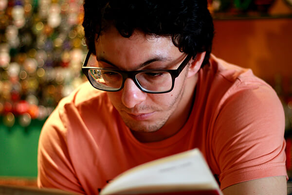 A man with glasses is reading, but it looks a little difficult.