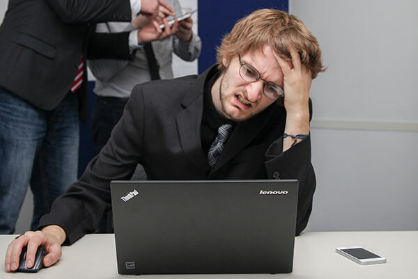 A man is looking irritably at the computer