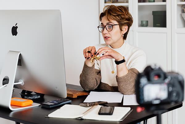 A woman wearing anti-blue glasses is working on a computer.