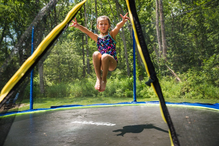 a girl cooling off on a Zupapa backyard trampoline in summer