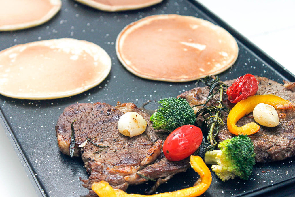Black griddle with steak and pancake on it
