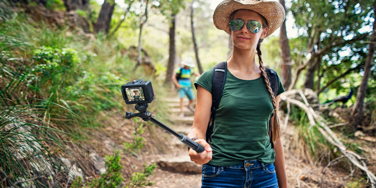 5 Reasons the COOAU-SPC03 Action Camera is the best for Beginners; A woman with an action camera walking in the forest.