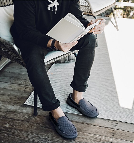 The model wears slippers and reads a book while sitting on a chair in the yard