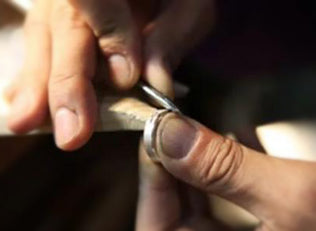 Carving the pattern on the ring with an awl by hand