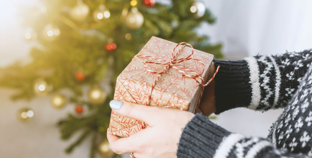 a woman holding a christmas gift box
