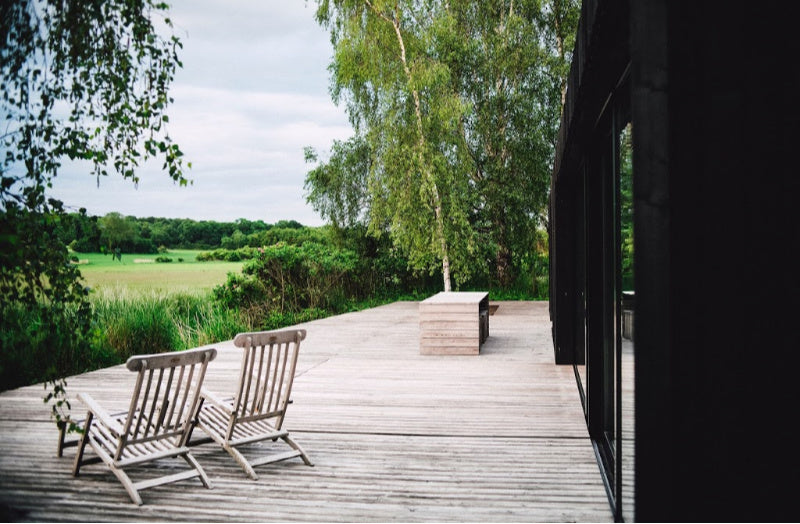 two wooden deck chairs on a wooden deck outside looking over a field