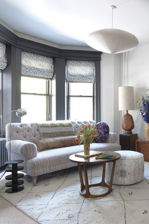 Roman shades form a decorative backdrop to a comfortable sitting room. The speckled pattern of grey and white draws the eye to the window. The striped upholstery and geometric Moroccan rug contrast with the circular design on the shades. The warm hue of the honey-colored wood furniture offsets the cold colors.