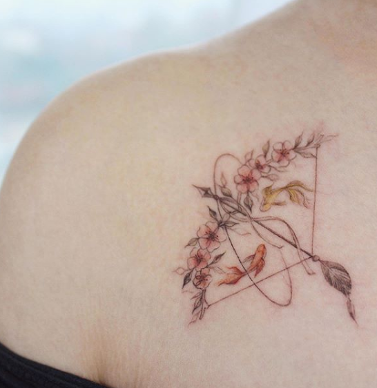 floral bow and arrow tattoo on chest