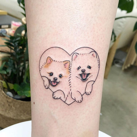 small dog tattoo in a heart frame