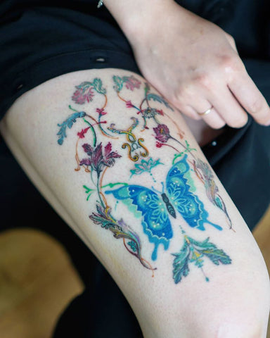 flower and butterfly thigh tattoo