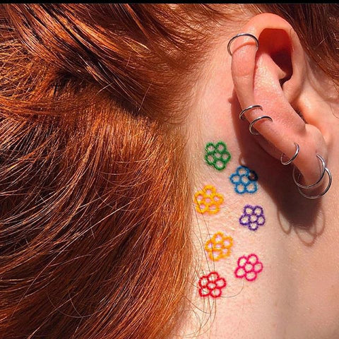 simple flower tattoo after the ear